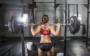 Sporty girl in a gym with a heavy barbell on her shoulders