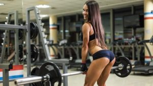 Beautiful girl in the gym with a barbell