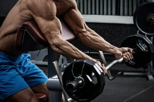 The athlete performs lifting the rod on the biceps in the cattle bench